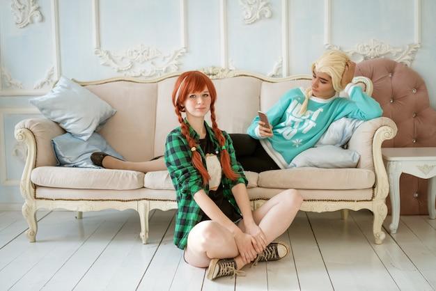 2人の友人、1人はソファに横たわり、2人目は隣の床に座って、リラクゼーションの概念