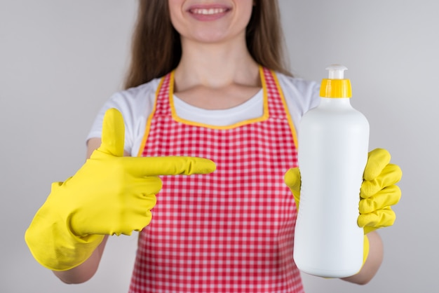 2 in 1 cream with glycerin and liquid chemical for plates concept. cropped close up  of satisfied cheerful with toothy smile wife holding bottle with fresh lemon aroma isolated grey wall