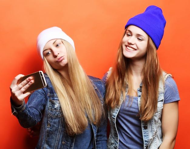 流行に敏感な衣装で2人の10代の少女の友人がフォーでselfieを作る