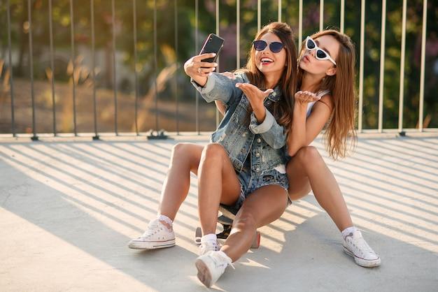 公園でスケートボードの上に座って流行に敏感な衣装で2つの10代のガールフレンドとスマートフォンでselfie写真を作る。幸せな友情とアクティブなライフスタイル。