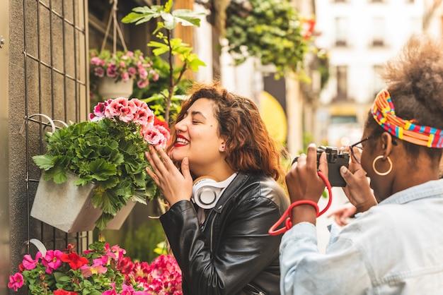 2人の10代の少女が花を嗅いでいます。
