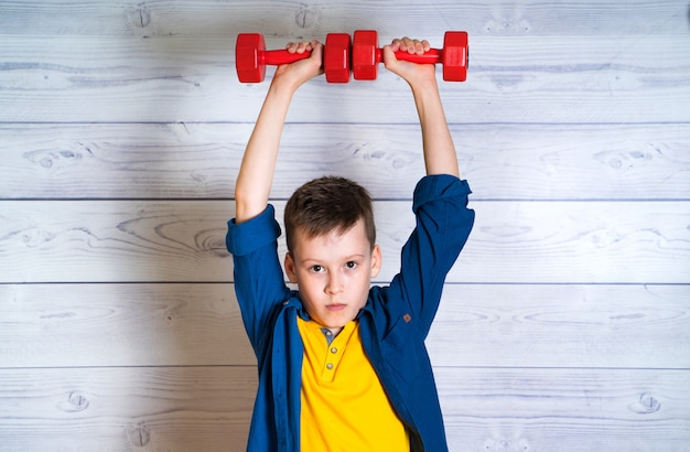 青いシャツを着た深刻な少年は、屋内で彼の頭の上にダンベルを保持しています。身体トレーニングの利点。 2つの赤いダンベル運動10代の少年
