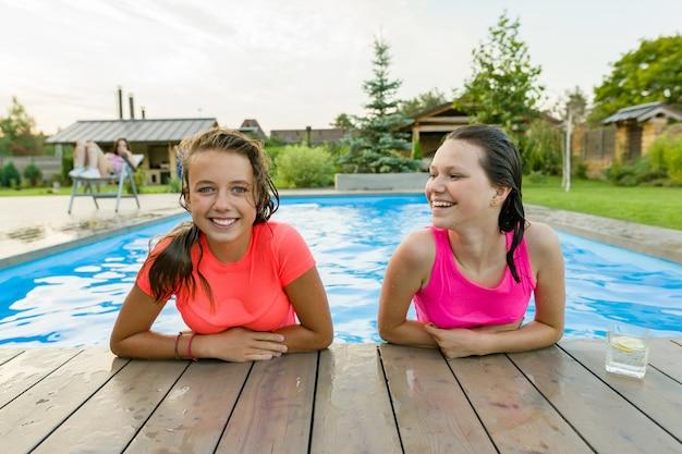 スイミングプールで楽しんでいる2人の若い10代の少女