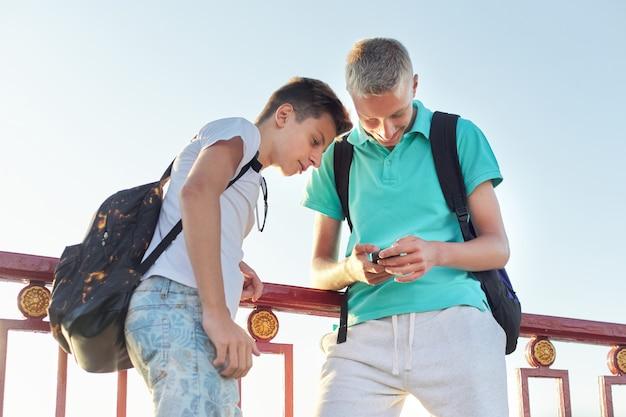 2人の友人10代の少年がスマートフォンを使用して、話して、笑って