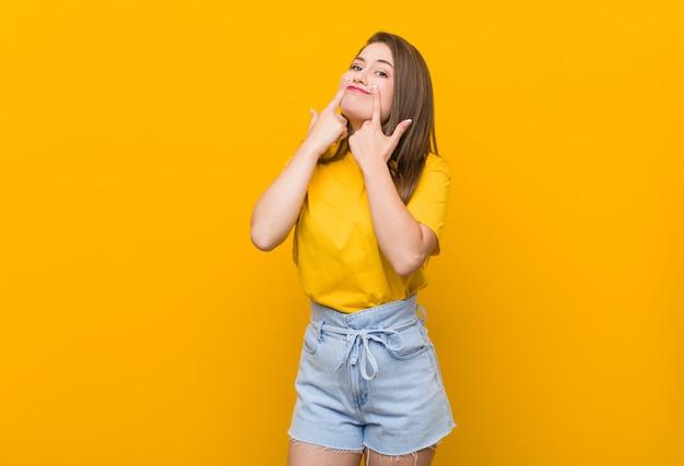 2つのオプションの間を疑う黄色のシャツを着ている若い女性10代。