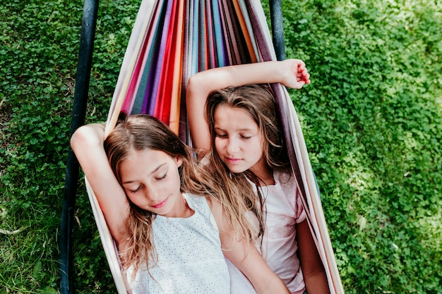 庭でカラフルなハンモックに横たわっている2つの美しい10代の女の子