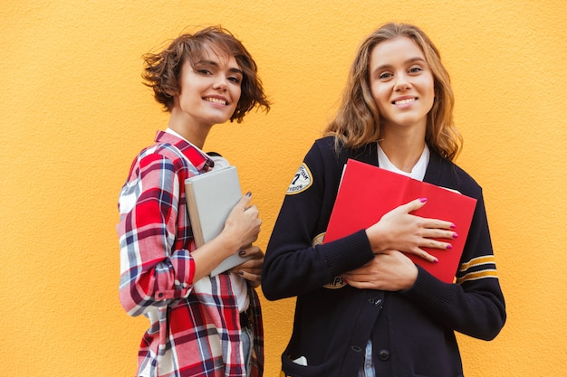 立っている本を持つ2つの若い10代の少女の肖像画