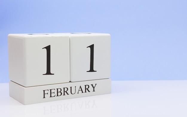2月11日月の11日目、白いテーブルに毎日のカレンダー。