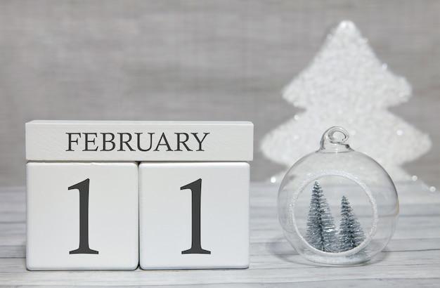 木製の表面と明るい背景に2月11日のキューブ形カレンダー