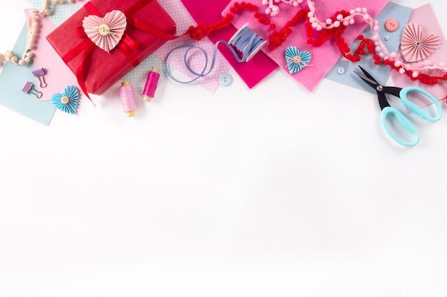 バレンタインの日と2月14日の休日のバナー。ギフト包装ワークスペース。装飾は、白い背景の上にフラットレイアウトトップビューお祝い準備diyコンセプト装飾を作ることを提示します。