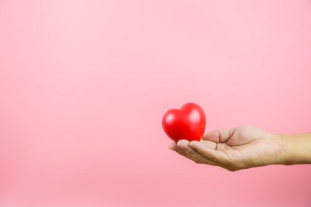 2月14日のバレンタインの愛と幸せな日のピンクの背景の概念に対して彼の手に赤いハート型の風船。