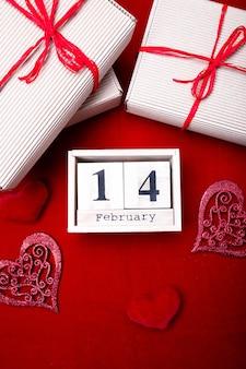 赤いハートとギフトボックスで2月14日の木製カレンダーショー。