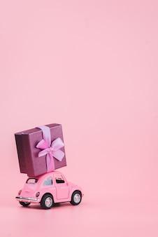 ピンクのレトロなおもちゃの車は、ピンクの背景にギフトボックスを提供します。 2月14日のはがき、バレンタインの日。花の配達。女性の日