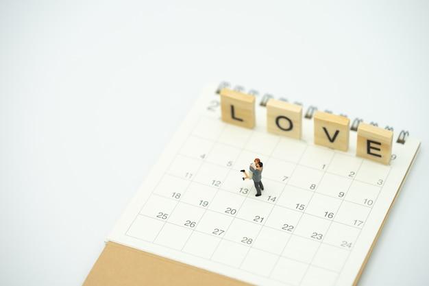 カップルミニチュア2人がカレンダーの上に立っています。 14日目はバレンタインデー