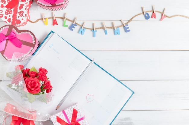 2月14日のギフトボックスと白い木の背景にバラの花束、バレンタインのカレンダーブック