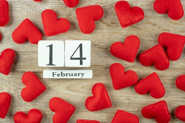 木製の2月14日カレンダーと赤いハート形の装飾。愛、結婚式、ロマンチックで幸せなバレンタインの日の休日の概念