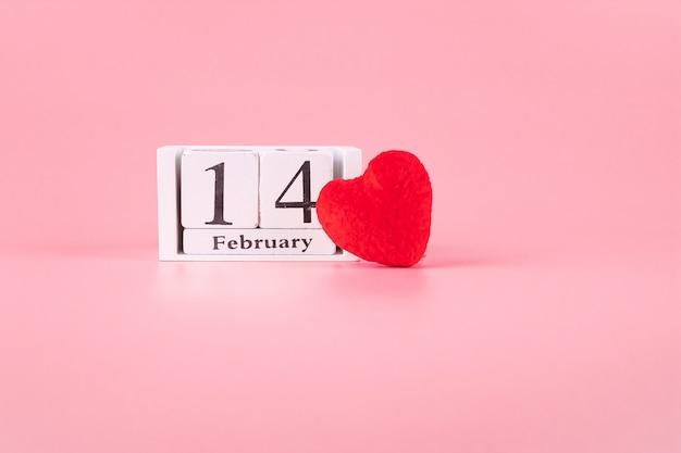 ピンクの2月14日カレンダーと赤いハート形の装飾。愛、結婚式、ロマンチックで幸せなバレンタインの日の休日の概念