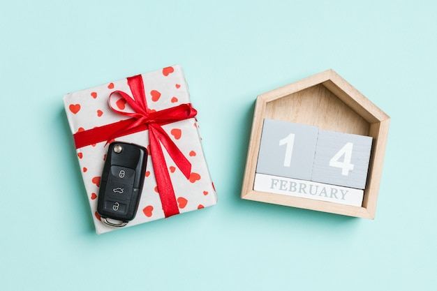 赤いハートとカラフルなお祝いカレンダーのギフトボックスに車のキーのトップビュー。 2月14日。バレンタインデーにプレゼント