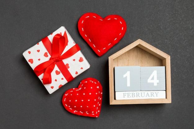 木製カレンダー、休日の白いギフトボックス、テーブルの上の赤い繊維心の組成。 2月14日。