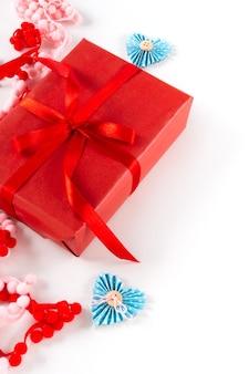 心と白い背景の上の弓と赤いギフトボックス。バレンタインデー2月14日のパッケージングコンセプト。