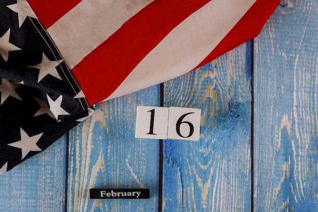 古い木の板に星とストライプのアメリカ国旗を美しく振る2月16日カレンダー。