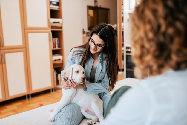 アパートで一緒に話している2人のガールフレンド、1人は子犬を保持しています。