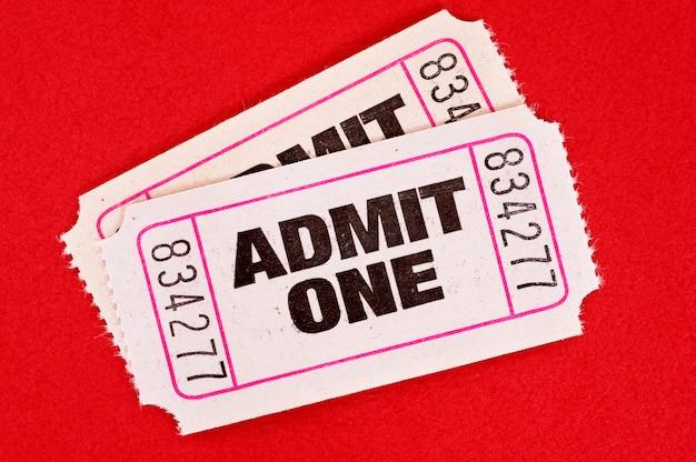 2人の白が赤の1つの映画のチケットを認めています。