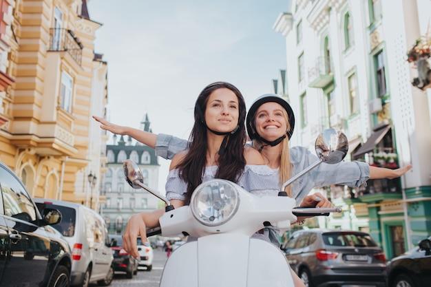 2人の女性が1つのバイクに乗っています。