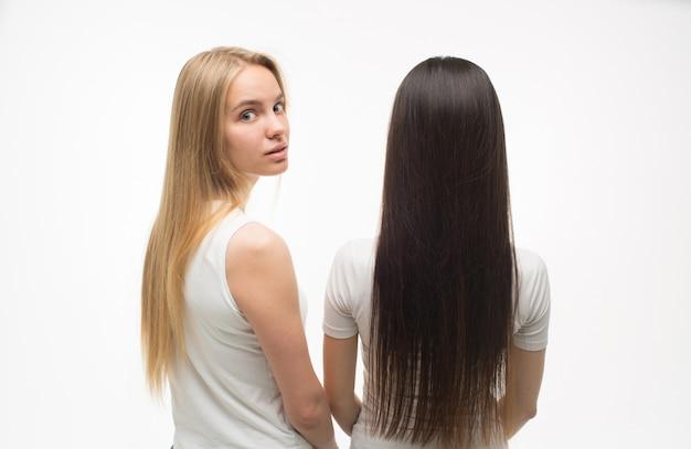2人の若い女性が立っており、1人は後ろ向き