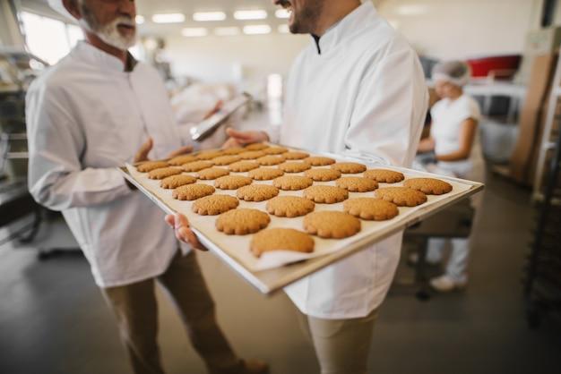 食品工場の大きなトレイに新鮮なクッキーのクローズアップ。背景で話している無菌の服を着た2人の男性従業員のぼやけた画像。1人の男性がトレイを保持しています。