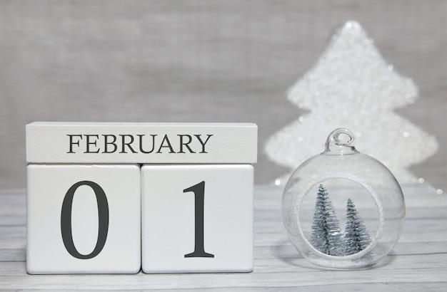 木製の表面と明るい背景に2月1日のキューブ形カレンダー