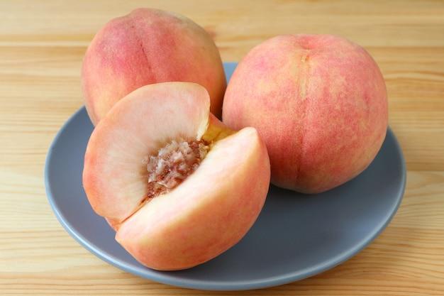 青い皿の上の2つの新鮮な熟した桃全体の果物と1つのカット桃は木製のテーブルで提供しています。