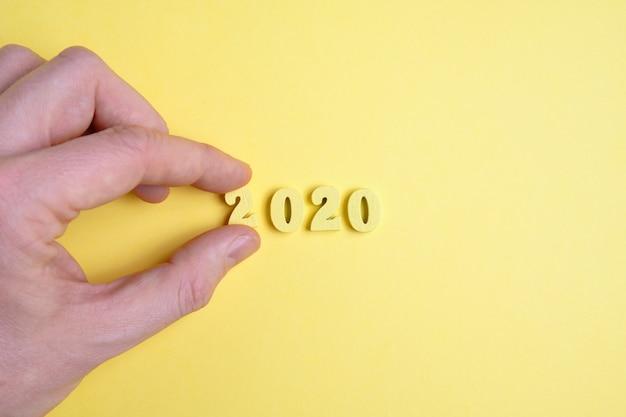 手は黄色の背景に並んで番号2を保持します。新しい年2020のコンセプト。
