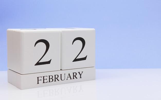 2月22日月22日、白いテーブルに毎日のカレンダー。