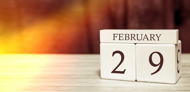 カレンダーのリマインダーイベントのコンセプト。 2月29日の数字と月の木製キューブ