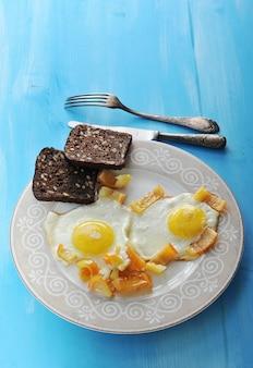 唐辛子とプレート、ナイフとフォーク木製の青い表面にライ麦パンの2つのスライスと2つの目玉焼き
