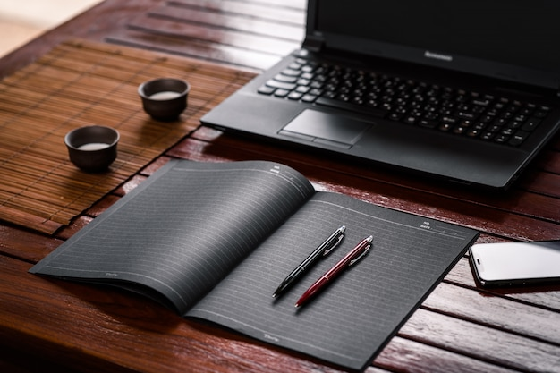 開いているノートパソコンと飲み物用のカップが2つある木製のテーブルの上に横たわる黒いノートにある黒と赤の2つのオフィスペン