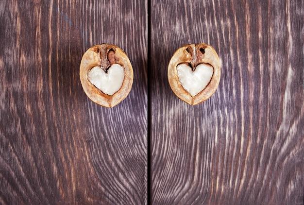 ハートの形のクルミの2つの半分は暗い塗られた木製のテーブルの2つの部分に横たわっています。