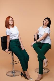 バースツールに座っている2人の同僚。バースツールでポーズをとって企業の2人のかなり若い成人女性の表情。