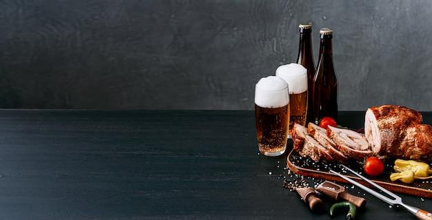 2つの肉とクラフトビールのディナー。ビール2杯、肉フォークとスパイスを木製のトレイに野菜と刻んだ肉を焼いた