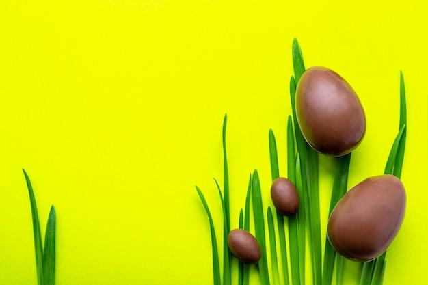 黄色の背景にイースターエッグ。緑の芝生に2つの大きなチョコレートの卵と2つの小さなチョコレートの卵。イースター休暇のコンセプトと楽しい。テキストのための場所。