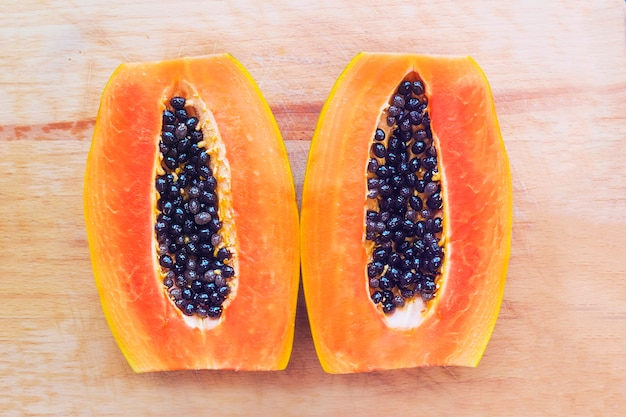 新鮮な熟した甘いパパイヤの2つの2つの半分は、種子、ピットで半分にカットします。エキゾチックなトロピカルフルーツ、健康的な生のビーガン、ベジタリアンフード。上面図。
