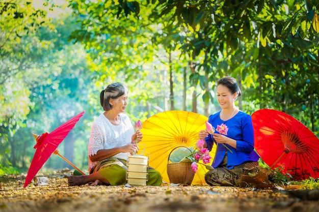 2人のタイ人女性、2人が今朝寺に行くためにピンクの蓮を折りたたんだ。