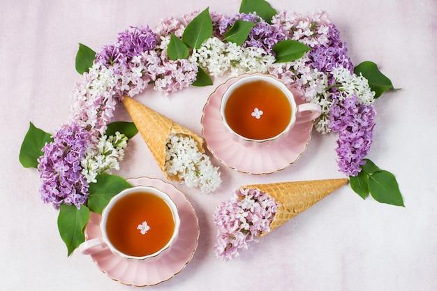 ピンクの背景にライラックのアーチ、紅茶2杯とライラックの枝を持つ2つのアイスクリームコーン