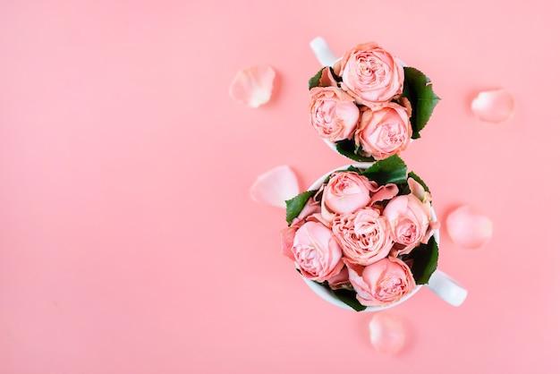 コピースペースのピンクの花とコーヒーを2杯と平面図。 3月8日の女性の日の背景。