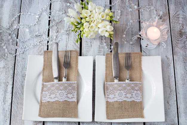 白い木製のテーブル、2つのプレート、キャンドル、フォークとナイフ、花瓶 - お祝い背景に花(誕生日、結婚式、3月8日、ロマンチックなディナー)
