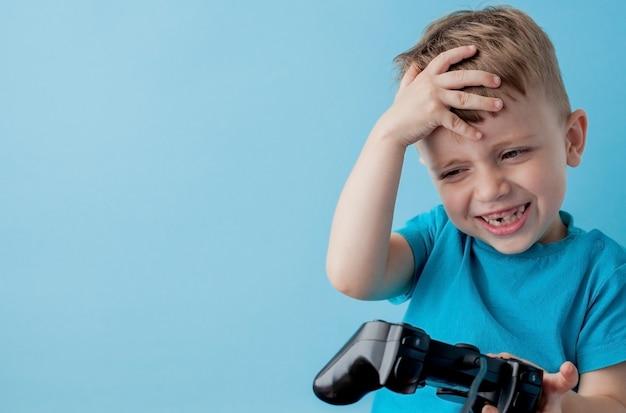 青い服を着て2〜3歳の小さな男の子は、ゲームソンブルーバックグラウンド子供スタジオポートレートのジョイスティックを手に保持します。人々の子供時代のライフスタイルのコンセプト。コピースペースのモックアップ