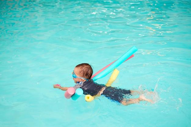 アジアの2〜3歳の幼児男の子は水泳のクラスを取り、子供はプールヌードルだけで浮かぶことを学ぶ、子供はおもちゃを保持し、屋内スイミングプールで彼の足を蹴る