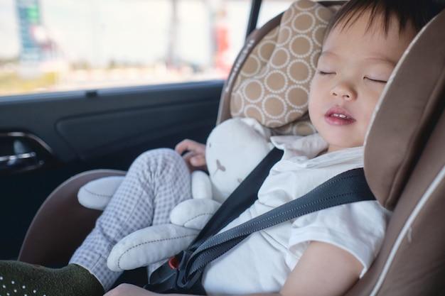 かわいい小さなアジア2-3年の幼児の男の子の子供は現代の車の座席で寝ています。道路上の安全な旅行の子供