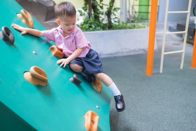 Азиатский малыш 2 - 3 лет с удовольствием пытается взобраться на искусственные валуны на детской площадке школьного двора, маленький мальчик взбирается по каменной стене